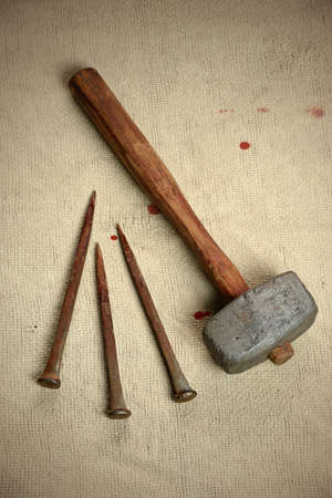 Ancient metal nails and hammer over vintage cloth with blood drops Stock Photo