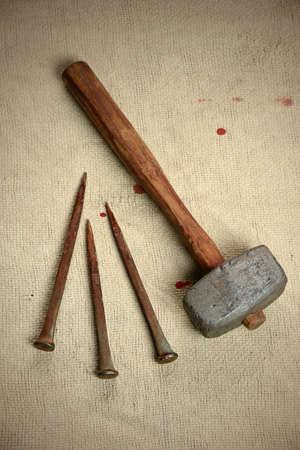Oude metalen nagels en hamer over vintage doek met bloeddruppels Stockfoto