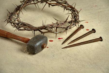 corona de espinas: símbolos cristianos de la crucifixión con corona de espinas, los clavos y un martillo en el paño en dificultades Foto de archivo