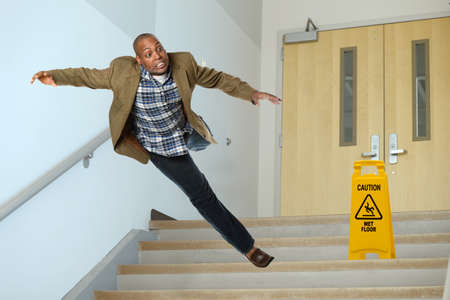 stairwell: African American businessman falling on stairwell with yellow warning sign on steps Stock Photo