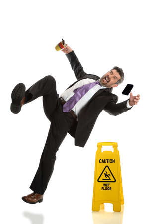 Hispanic businessman falling next to wet floor sign isolated over white background Foto de archivo