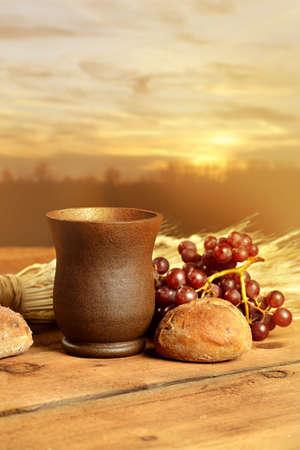 Abendmahlskelch mit Brot, Trauben und Weizen auf Holztisch Standard-Bild - 56584504