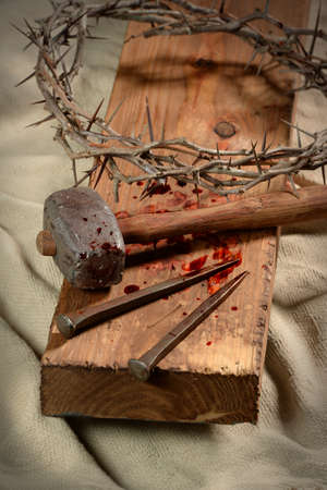 passion of the christ: Cross with crown of thorns, nails and hammer over old cloth