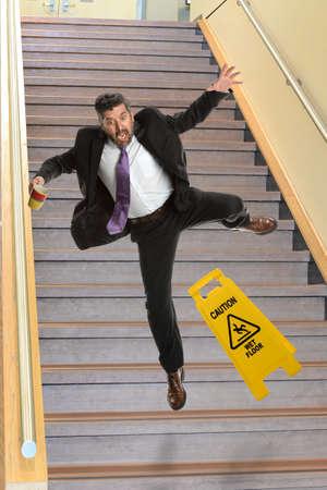 Mature Hispanoc businessman falling on stairs