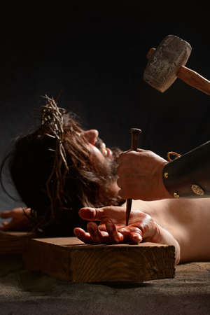 nailed: Jesus hand being nailed to the cross by Roman soldier