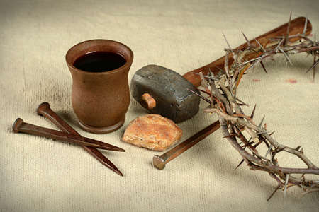 Communion elements with crown of thorns and nails over vintage cloth
