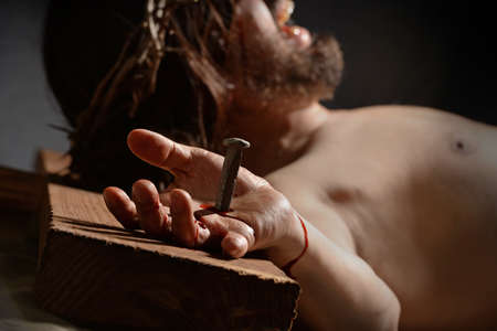 redemption: Jesus  on the cross with nail and hand in foreground