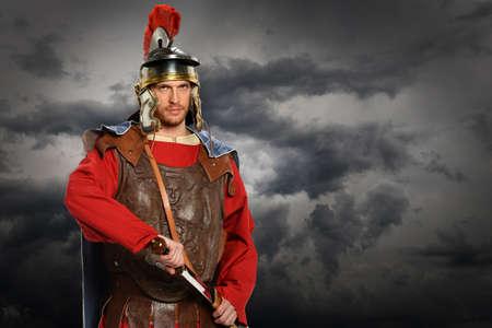gladius: Portrait of Roman soldier with sword 0ver stormy sky