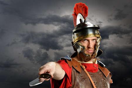 gladius: Portrait of Roman soldier brandishing sword over dark clouds