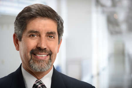 Portrait of mature Hispanic businessman smiling inside office building Archivio Fotografico