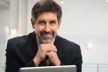 mature businessman: Portrait of senior Hispanic businessman using laptop inside office building