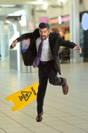 Hispanic senior businessman slipping on wet floor inside building
