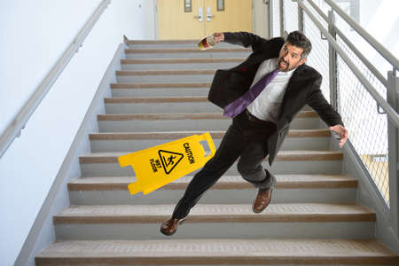 Mature Hispanic businessman falling down the stairs Stockfoto