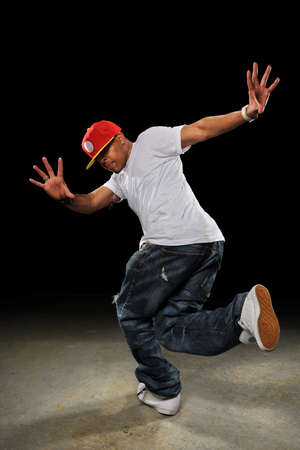 rapping: Young African American hip hop dancer performing over dark background Stock Photo