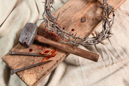 Crown of thorns, nails, and mallet over vintage cloth Stockfoto