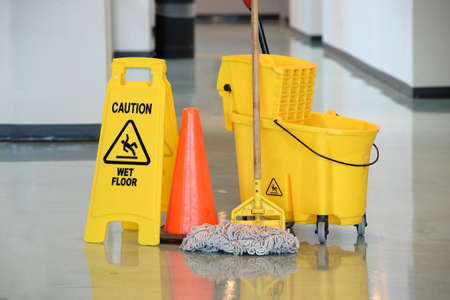 Caution sign with mop and bucket on office floor