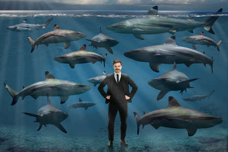 Confident young businessman surrounded by sharks underwater Stock Photo