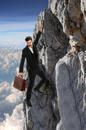 clinging: Young businessman clinging onto rock with clouds in background Stock Photo