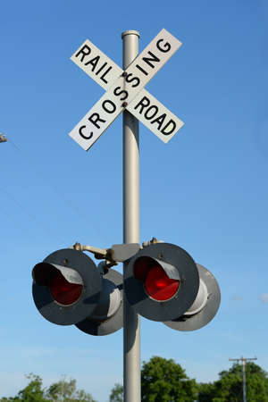 Railroad sign post during daytime with red light on Stock Photo