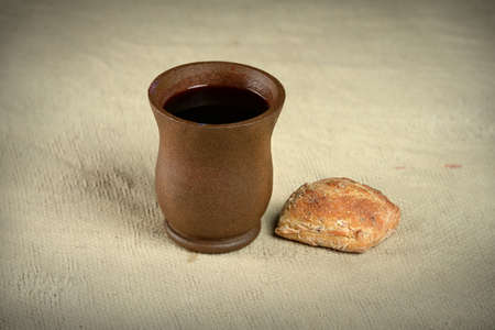 一杯のワインとビンテージ布の上パン