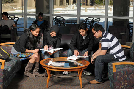campus building: Ethnically diverse group of students studying inside campus building Stock Photo