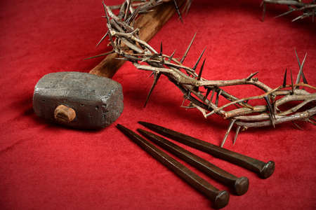 Crown of thorns, nails and hammer representing crucifixion symbols on red cloth Archivio Fotografico