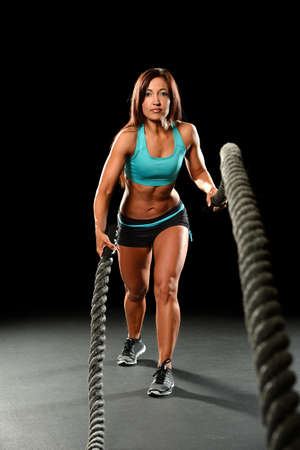 rope: Portrait of young woman working out with heavy ropes over dark background