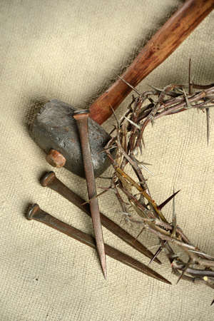 Crucifixion tools including crown of thorns, nails, and hammer over vintage cloth