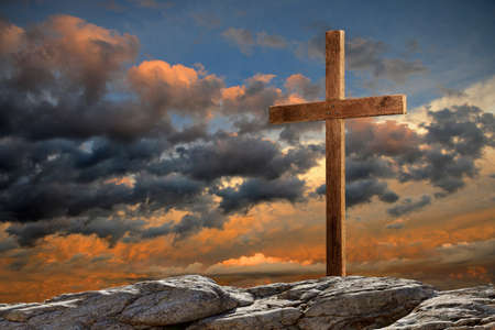 biblical: Wooden cross on rocky hill at sunset
