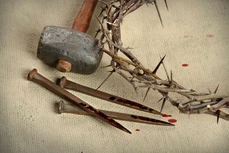 Crown of thorns, nails and hammer over vintage cloth Stockfoto