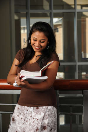 campus building: Portrait of athnic female student reading book inside campus building