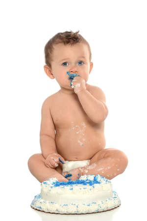 baby sit: Portrait of infant eating birthday cake isolated over white background Stock Photo