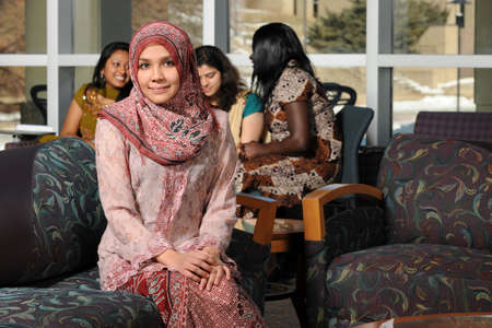 bilding: Portrait of young Muslim woman with headscarf inside college bilding on campus Stock Photo