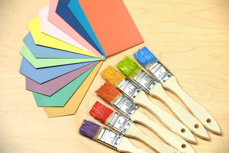 assortment: Assortment of color samples and paintbrushes over table