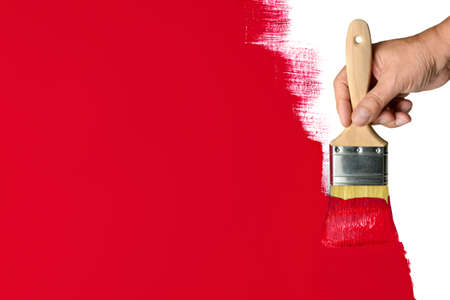 Man's hand using paintbrush with red paint on wall Stockfoto