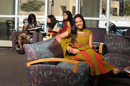 ethnically diverse: Group of ethnically diverse group of young women inside college campus building Stock Photo