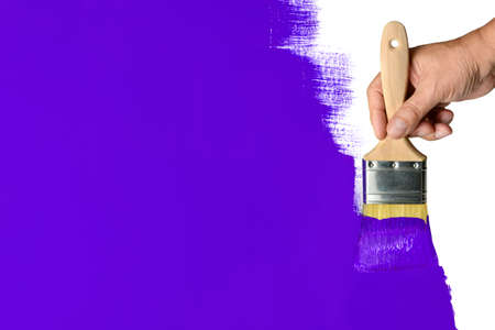 brush painting: Mans hand using paintbrush with purple paint on wall
