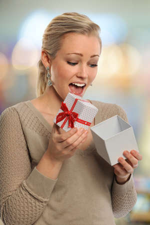reacting: Young woman reacting with surprise when opening gift box