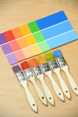 paint samples: PAintbrushes with different colors with paint samples on wooden table