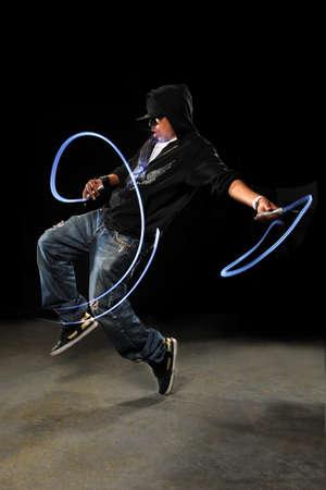 African American hip hop dancer with LED lights over dark background photo