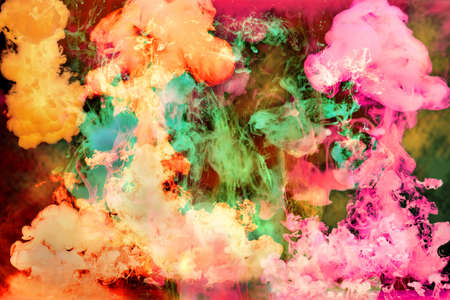 dynamic movement: Colorful bright inks disolving in water over a dark background Stock Photo