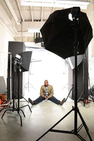 photo studio: Young African American businessman sitting on floor of photo studio