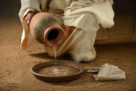 Jesús verter agua de jarra en sartén sobre fondo oscuro Foto de archivo - 63773666