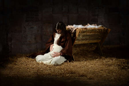 Pregnant Mary leaning on the manger on Christmas Eve