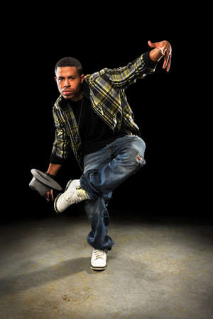 hip: Young African American hip hop dancer performing over dark background Stock Photo