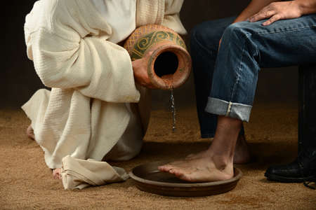 Jesus pouring water to wash feet of modern man over dark background