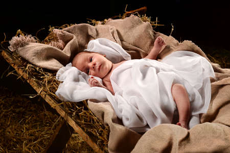 Baby Jesus when born on a manger wrapped in swaddling clothes over dark background