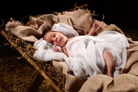 Baby Jesus när han föddes på en krubba inslagna i swaddling kläder över mörk bakgrund Stockfoto