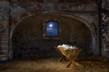 nacimiento: pesebre vacío en el antiguo granero con ventana que muestra la estrella de Navidad