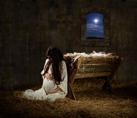 Young pregnant Mary praying leaning on manger on Christmas Eve 스톡 콘텐츠